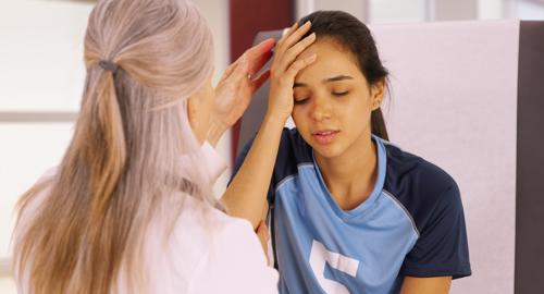 A girl having a head injury examined by a doctor.