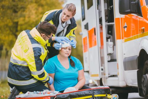 A woman having an injury to her head treated by paramedics.